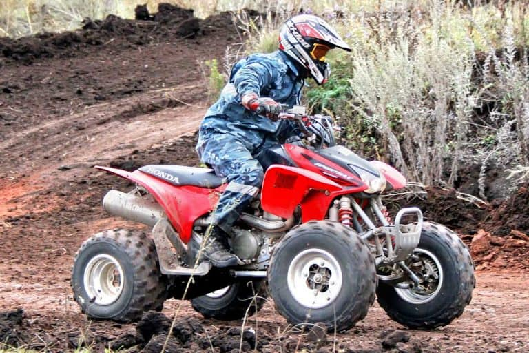 ATV rider in action racing with quad bike on a muddy road, Does the Honda 90 ATV Have Reverse?