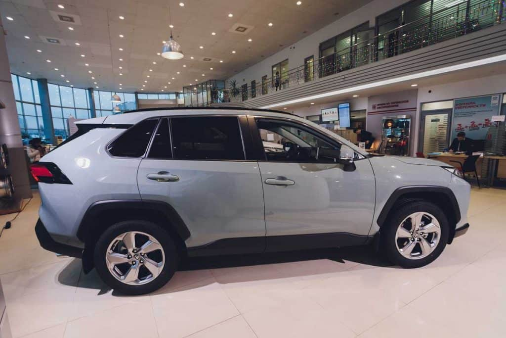 All-new compact crossovers Toyota RAV4 premier at Toyota car standing next to showroom entrance , side view