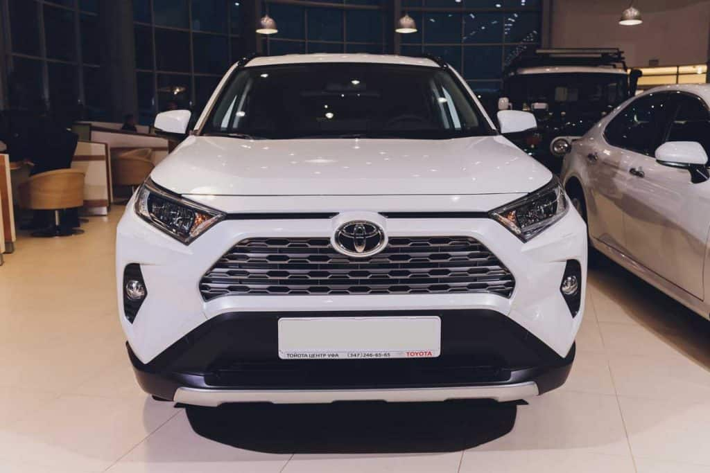 All-new compact crossovers Toyota RAV4 premier at Toyota car standing next to showroom entrance front view