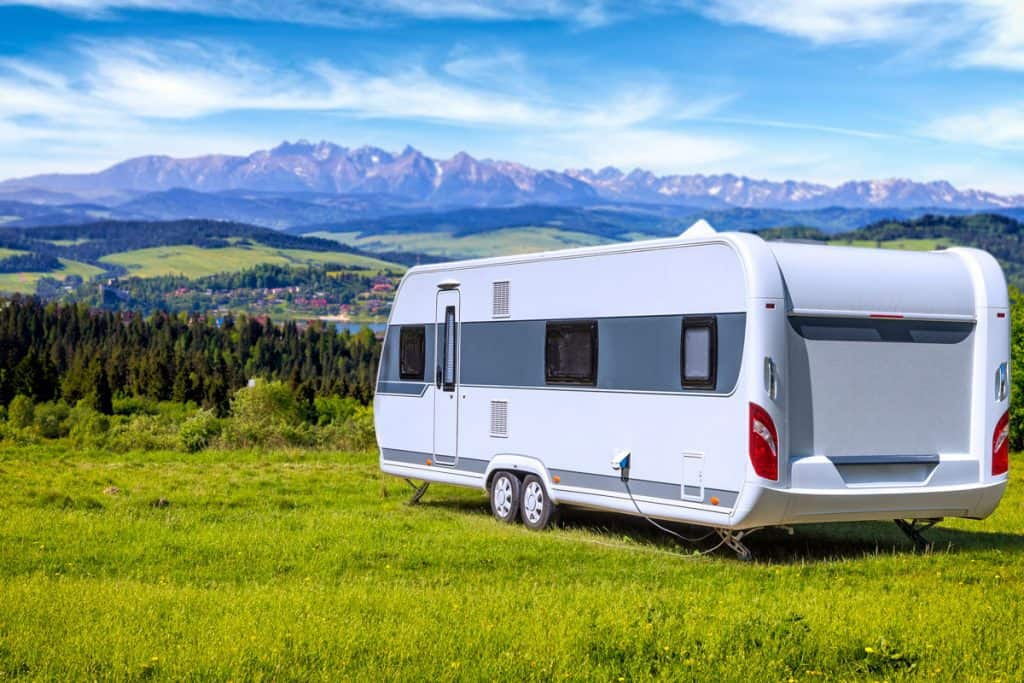 An Artic Fox RV parked on a hill with a panoramic view of a town surrounded by mountain ranges and blue skies, Arctic Fox North Fork Travel Trailer Floor Plans & Features Guide