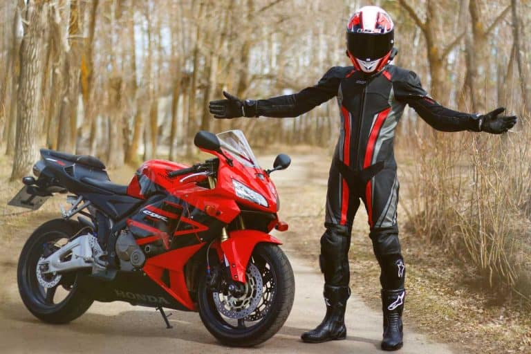 Beautiful motorcyclist in full gear and helmet with a red and black motorcycle, Does Jeep Renegade Come With A Spare Tire?