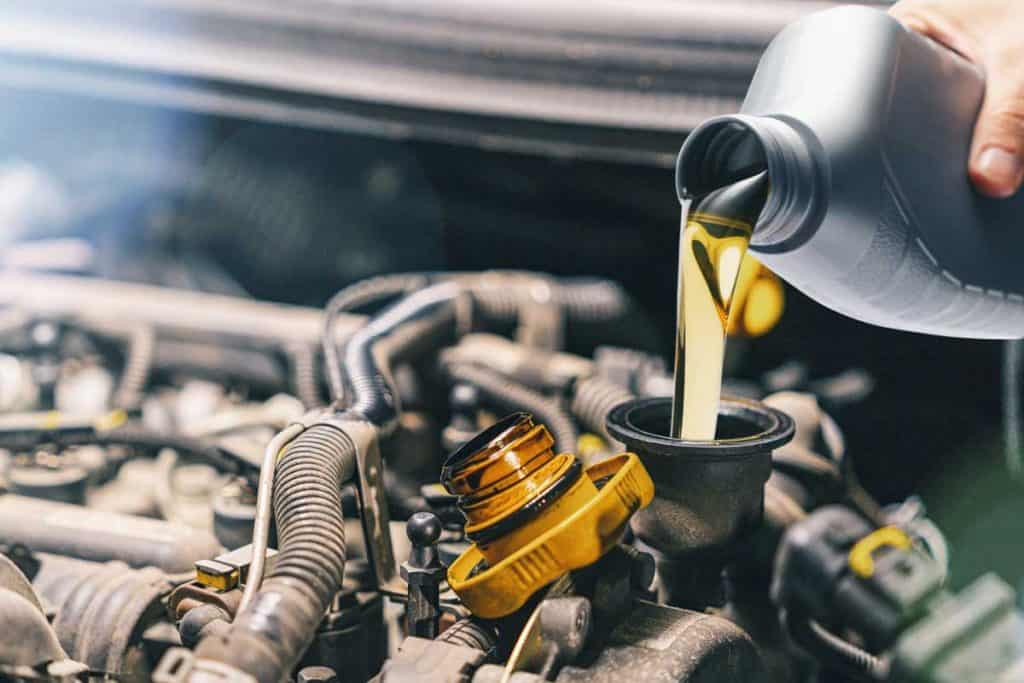 Fresh motor oil poured to car engine, Will Synthetic Oil Make Your Engine Last Longer?