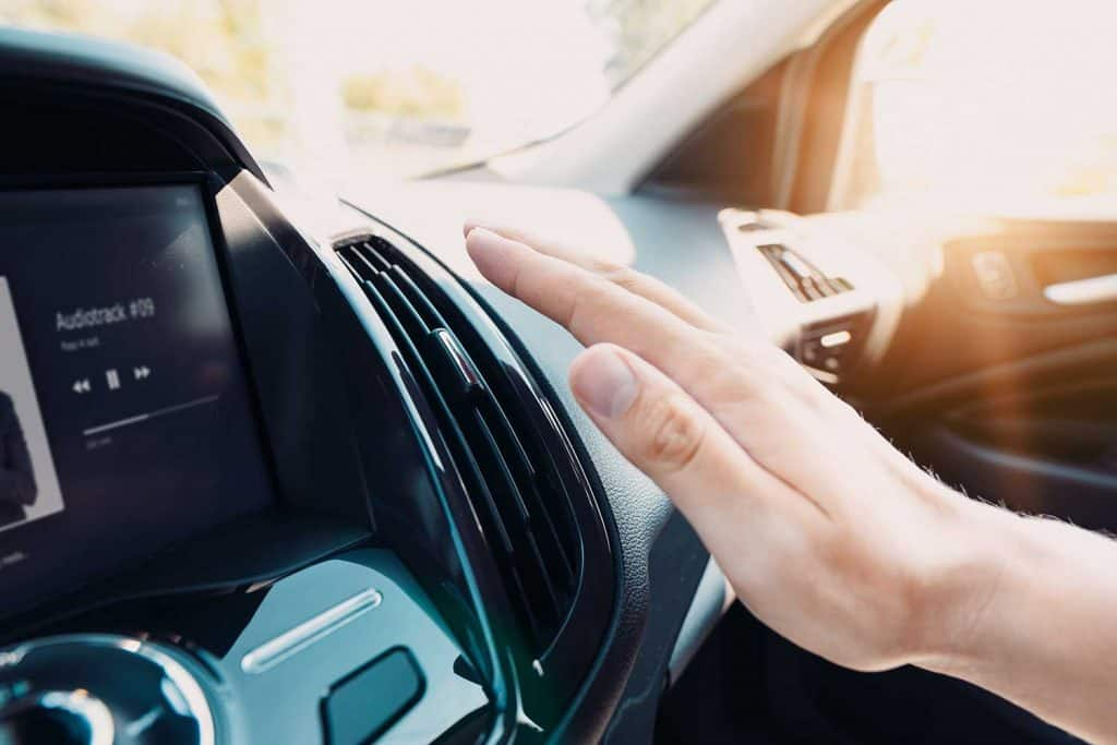 Hand checking the air conditioner in the car
