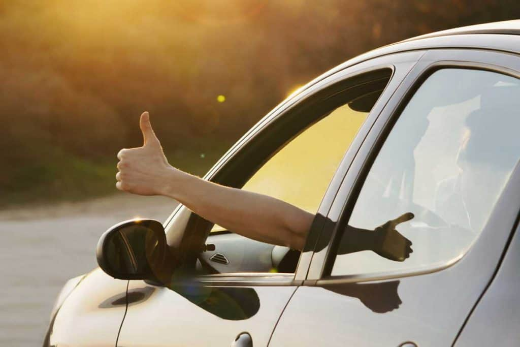 Man showing thumbs up from car window at sunset, Do I Need To Warm Up My Car Before Driving?