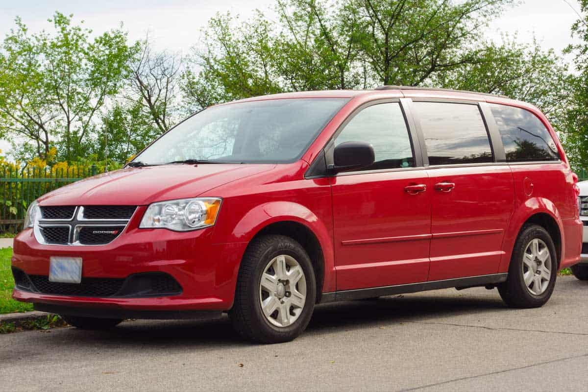 Red colored Dodge Grand Caravan minivan parked on the street, Here's What The Dodge Grand Caravan Interior Is Like