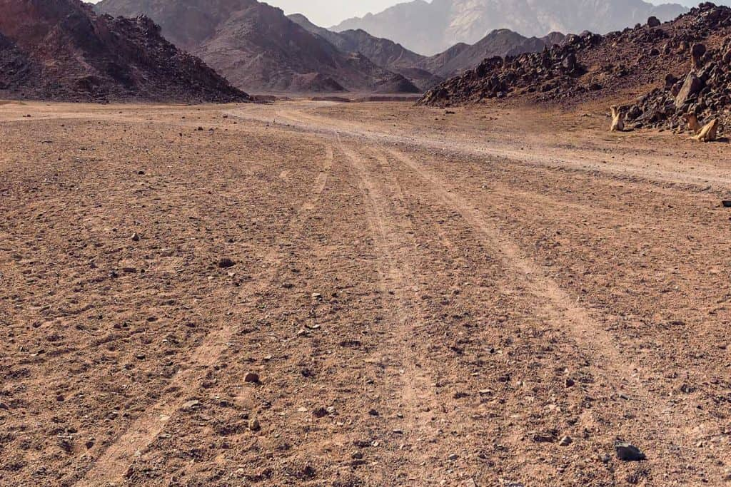 Rough terrain with tracks from cars in a desert, How Much Does A Sherp ATV Cost?