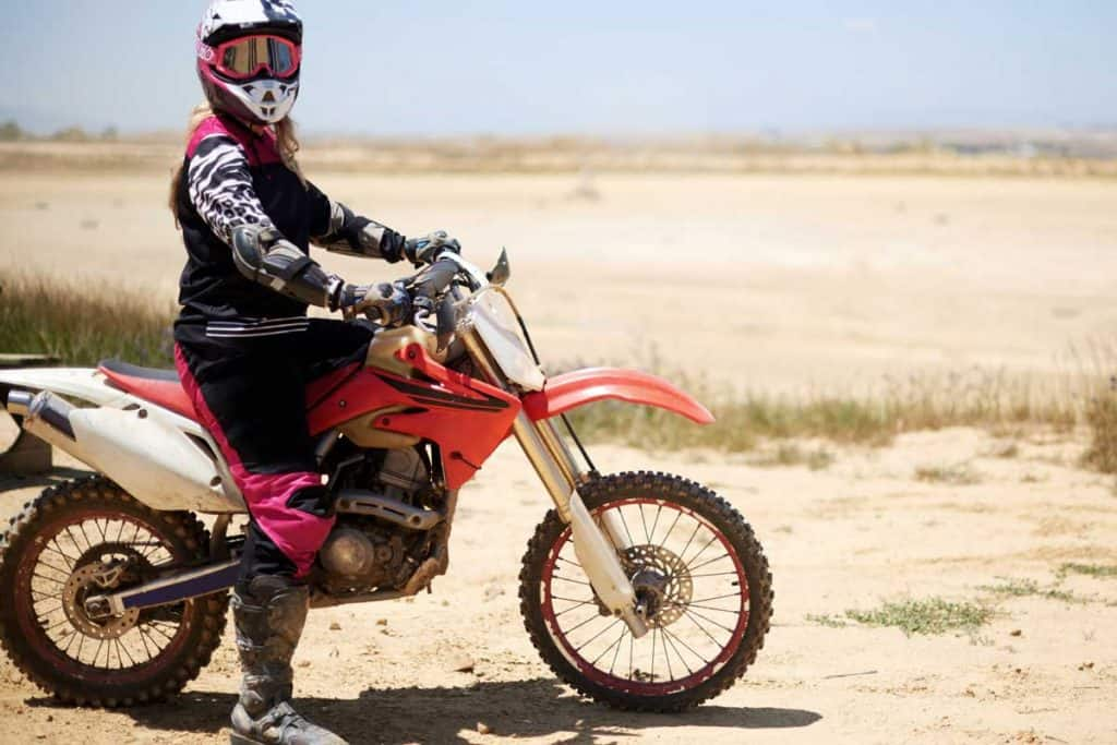 Shot of a young woman riding her dirt bike on an outdoor track