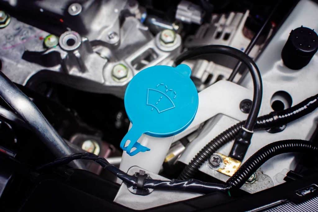 Windshield washer fluid cap with blue color in engine room of car