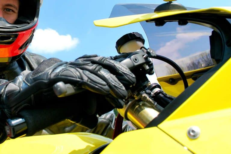Yellow biker wearing leather gloves on a sunny day, 16 Types of Motorcycle Gloves You Need to Know