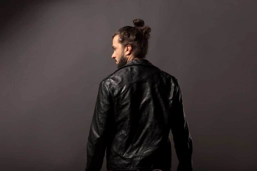back view of man with beard and bun in black leather jacket, How To Wear Your Hair When Riding A Motorcycle?