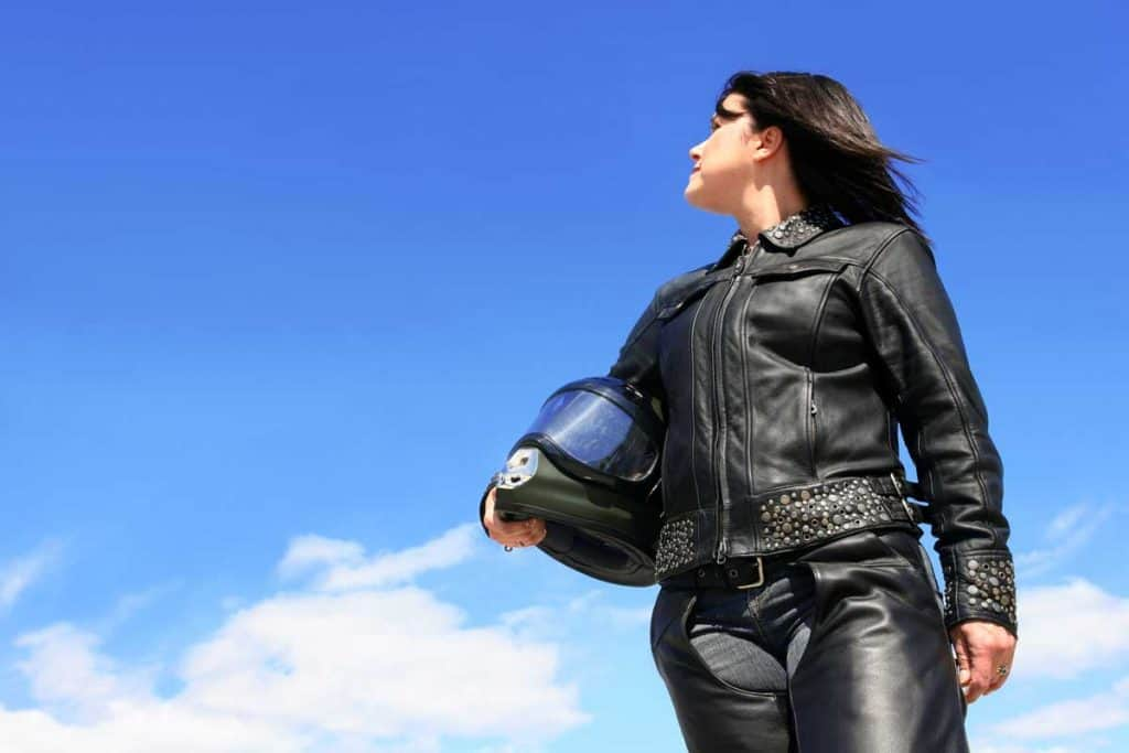 female biker in leather jacket and chaps holding a helmet looking to her right.