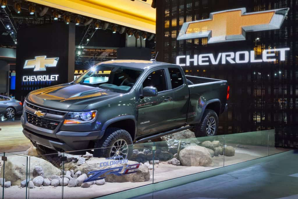 A Chevrolet Colorado on a rocky terrain display at a car show, How Often to Change Spark Plugs in a Chevy Colorado?