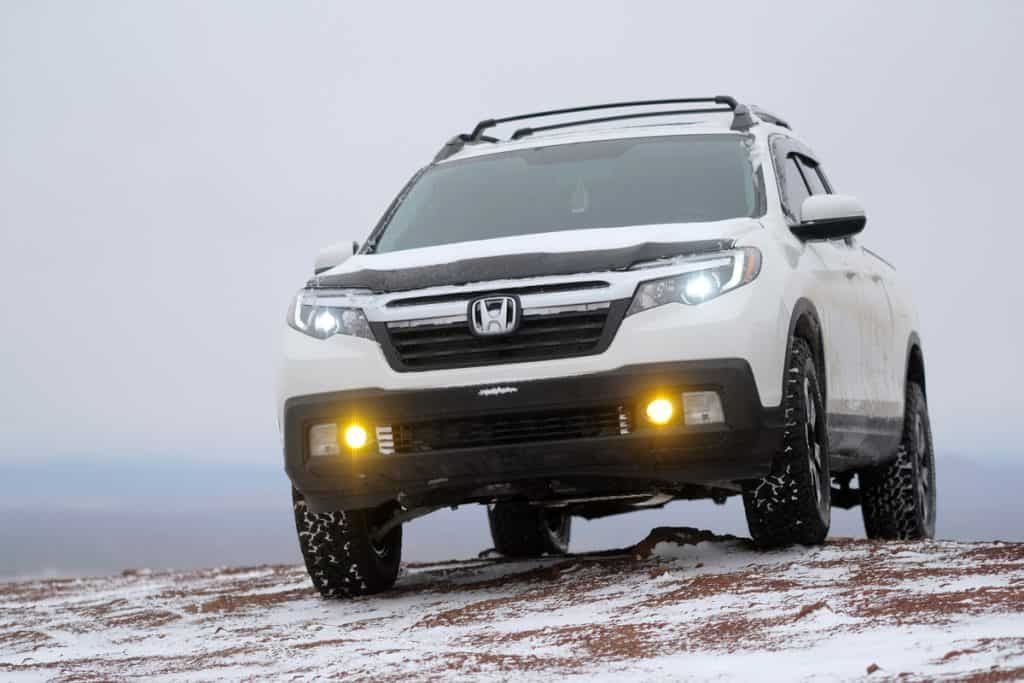 A Honda Ridgeline trekking on a snowy terrain under heavy fog with low visibility, Is the Honda Ridgeline a 4WD?