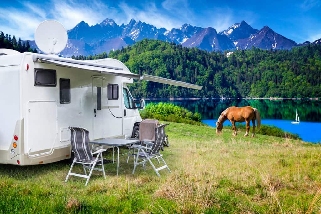 A RV parked near a lake with a panoramic view of the crystal clear waters of a lake and tall mountains, 12 Best RVs for Full-Time Family Living [By RV type]