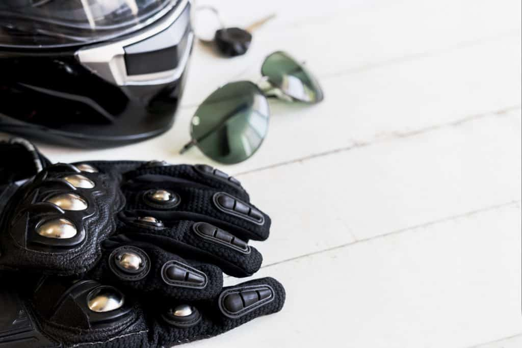 A black motorcycle glove with metal plated knuckles and a helmet on the table, How To Wash Motorcycle Gloves? [3 Steps]
