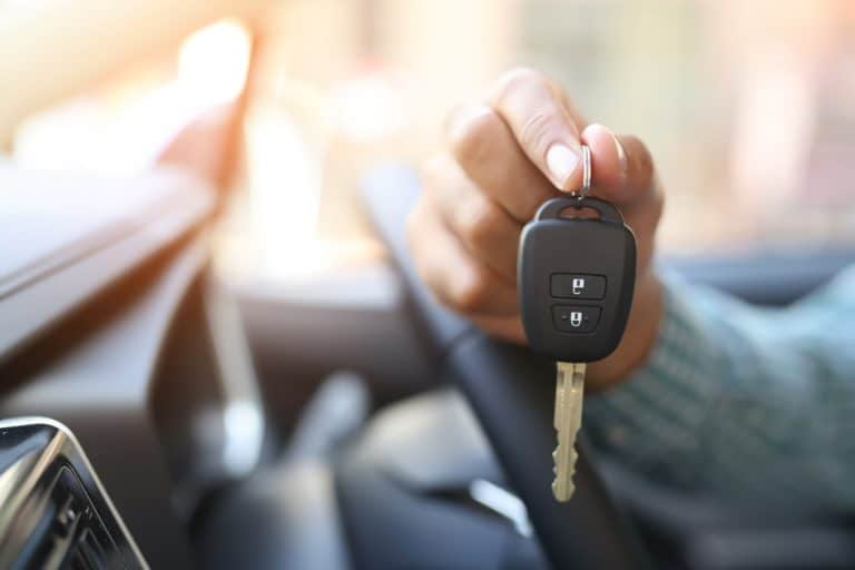 A man holding the car key of his convertible car, Can A Car Key Get Worn Out? (And What To Do About It)