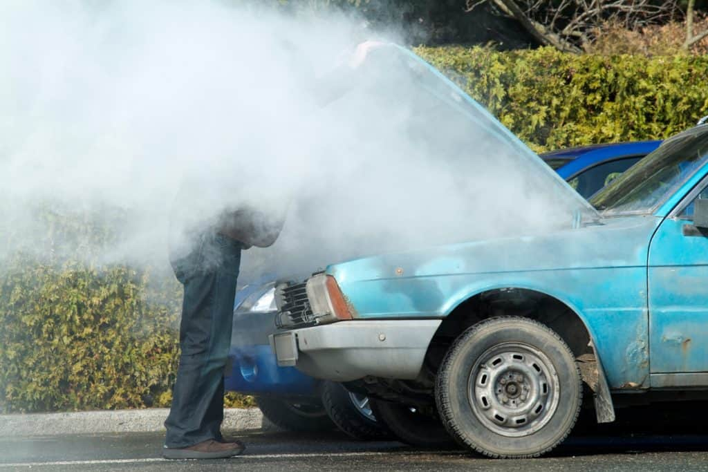 A man opening his car engine due to overheating