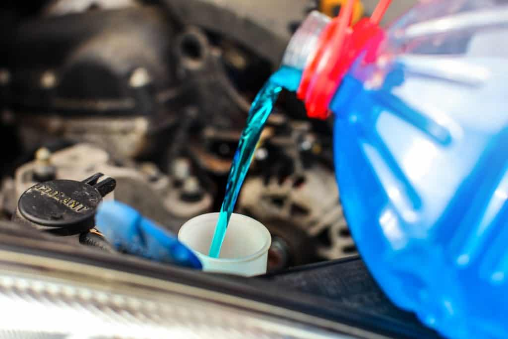 A mechanic pouring engine coolant in to the coolant intake of the engine