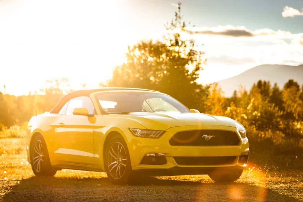 A yellow convertible Ford Mustang photographed at dawn, 21 Types Of Ford Cars [And that's without trucks!]