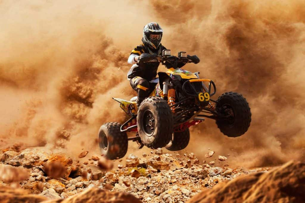 ATV in dust cloud, sand quarry on background