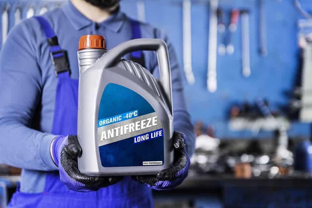Auto mechanic showing antifreeze plastic container in the auto repair shop