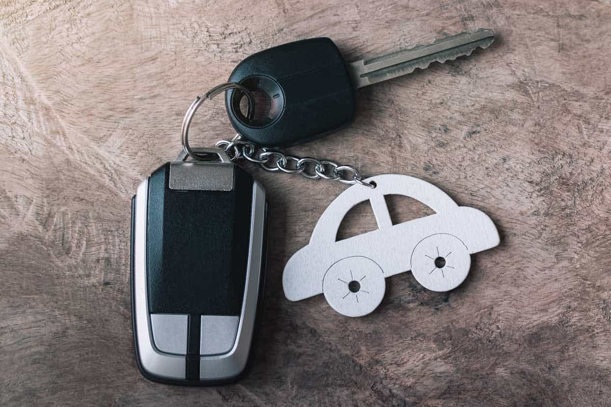 Car key and remote with car keychain on an old wooden table, Where Should You Leave Your Car Keys At Night?