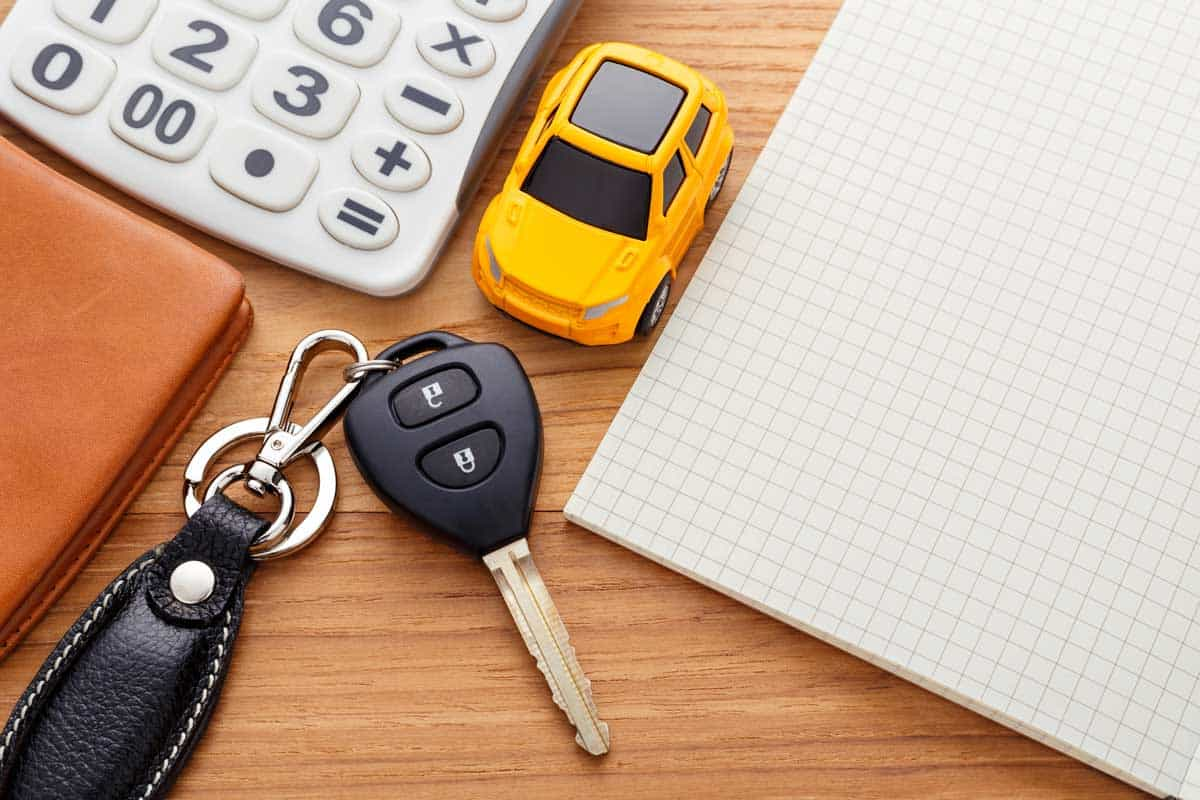 Car key with notebook calculator and pocket money on wood table, Are Car Keys Magnetic? [Here's What They're Made Of]