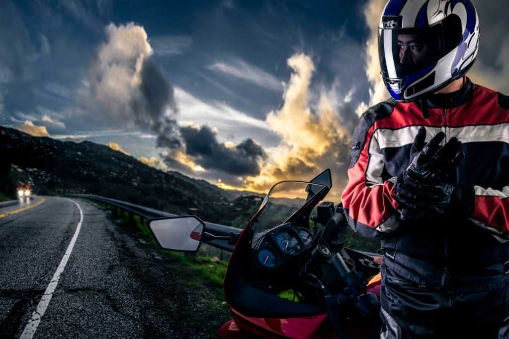 Male motorcyclist wearing protective leather racing suit with a red bike or motorcycle on an open road, What's The Average Cost For Motorcycle Gear?