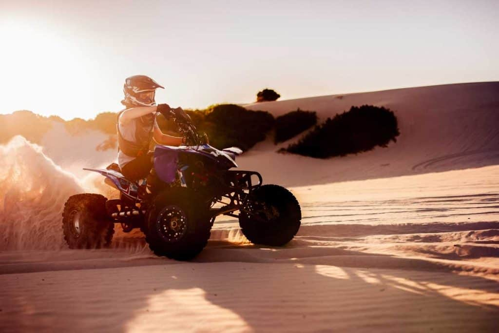 Professional quad bike racer driving on sand dunes in protective gear