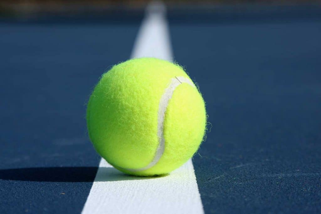 Tennis ball centered on the court line