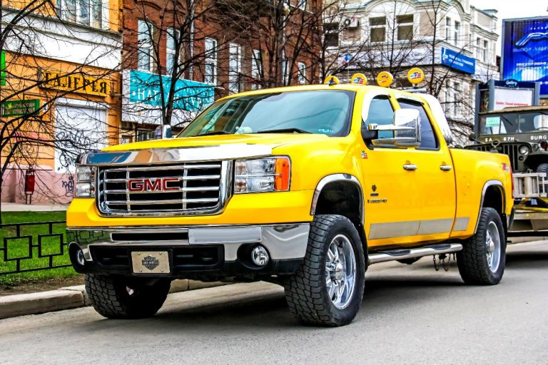 yellow GMC Sierra parked along the street