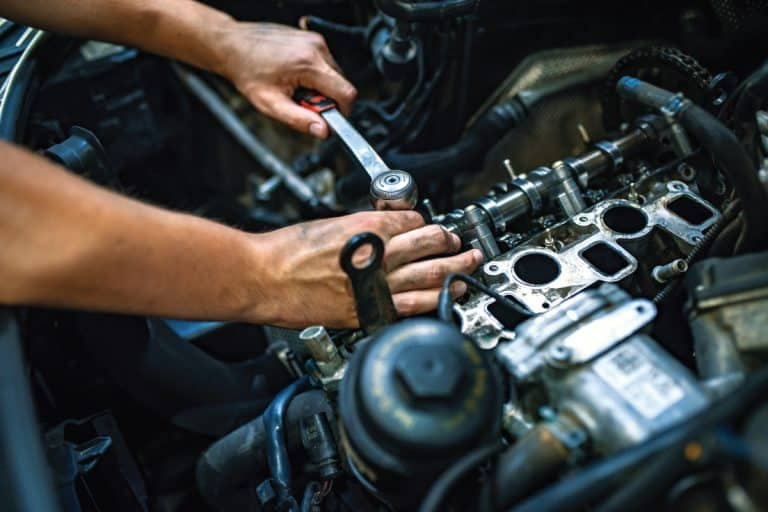 mechanic using ratchet while repairing engine, how long does it take to replace an engine