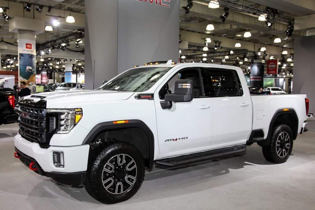 white gmc sierra on display in a car showroom