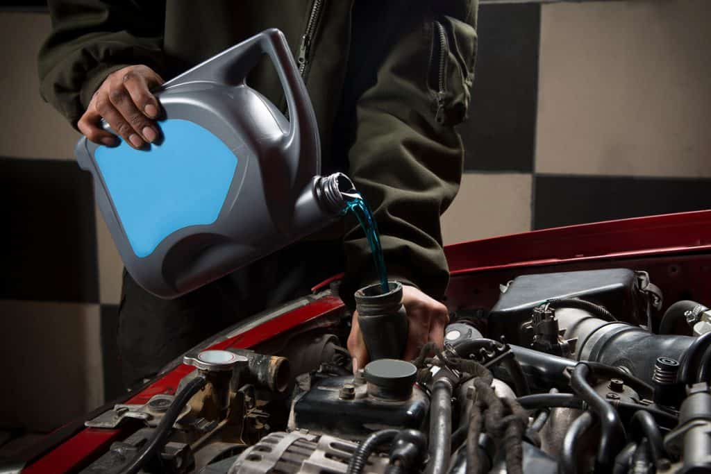 A man pouring coolant into the coolant intake of a car engine, Coolant Level Low When Cold - What To Do?