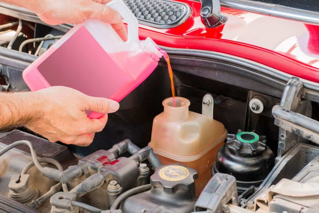 A man pouring coolant on the engine