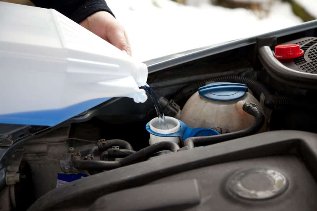 A mechanic pouring coolant on the engine of a car