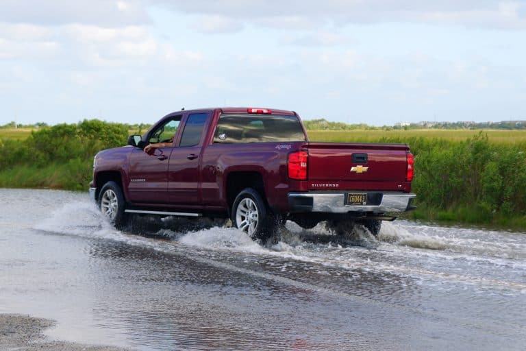 A red Chevrolet Silverado moving on a flooded road, Can a Chevy Silverado Be Flat Towed? Here's What Truck Owners Need to Know
