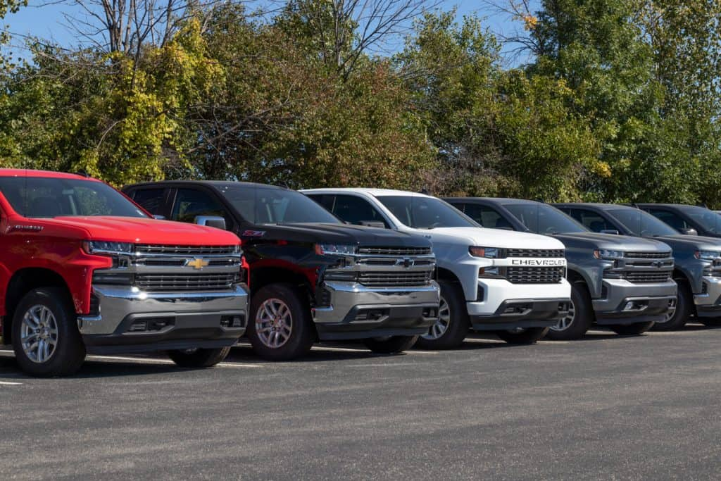New different colored Chevy SIlverados lined up displayed on a car dealership, Does Chevy Silverado Take Regular Gas Or Diesel?