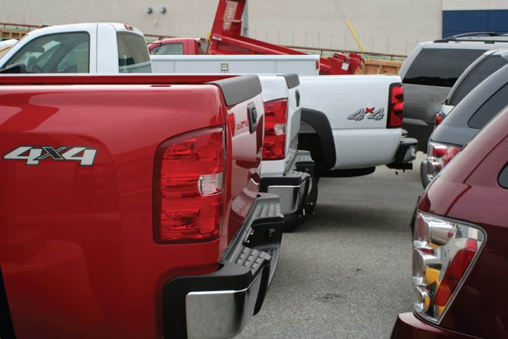 Assorted pickup trucks and SUVs in a car dealership, How Much Weight Can A Truck Carry [By Truck Type]