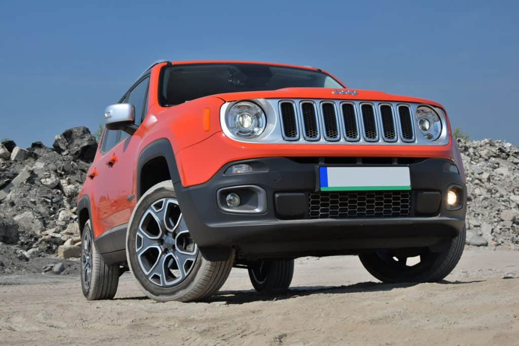 Brand new red Jeep Renegade photographed on a rocky terrain, How Many Miles Can a Jeep Liberty Last?