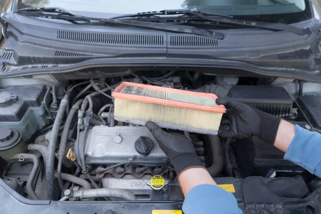 A car mechanic removing and showing an old car air filter