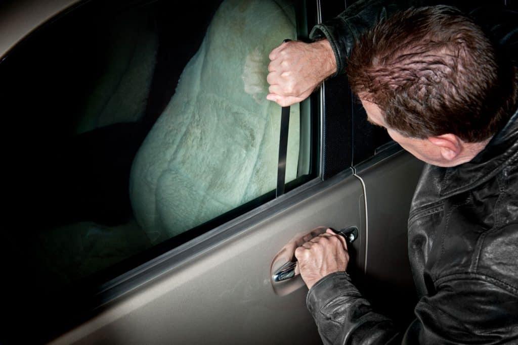 A car thief using a piece of metal to unlock a car