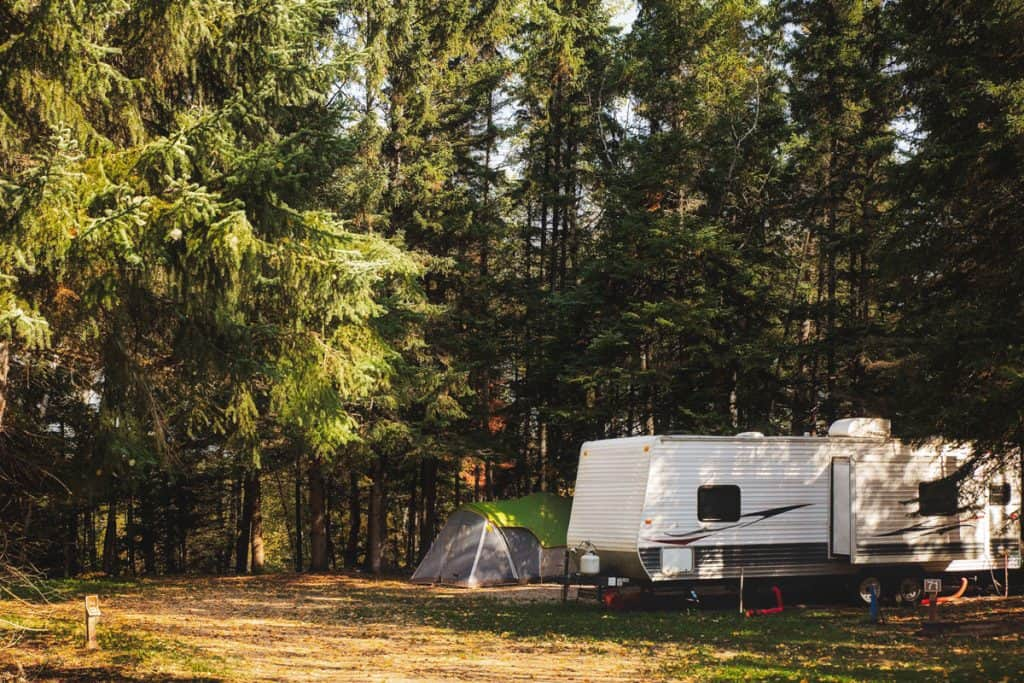 Fifth wheel parked on a pine tree forest with tents set up outside, What Bathroom Accessories Should You Get For A New RV?