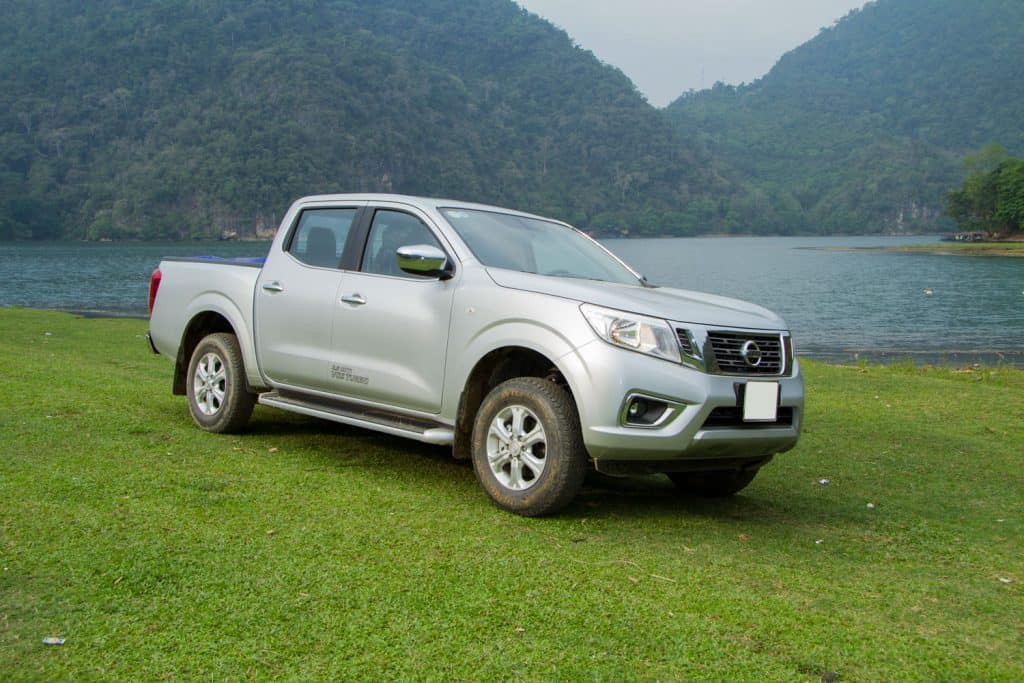 A gray Nissan Frontier parked near the side of a lake