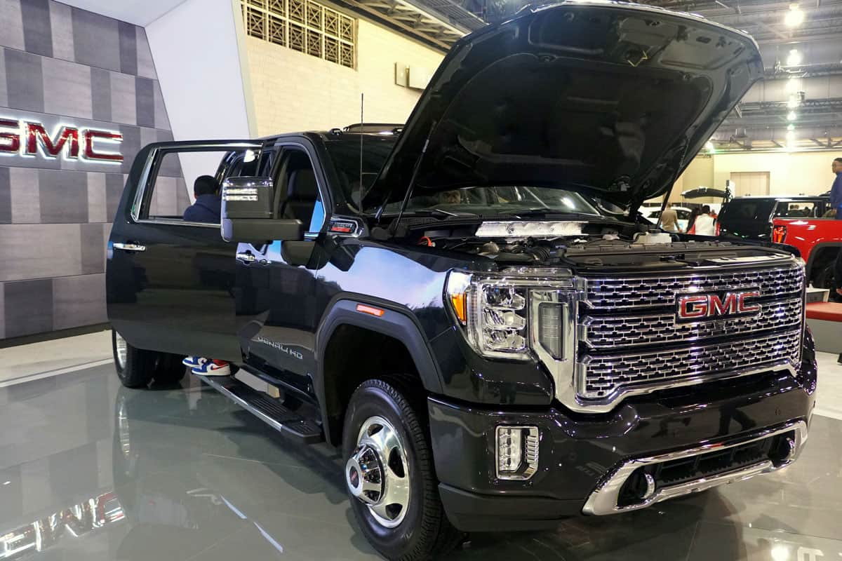 Huge dual rear GMC Sierra 3500 HD with an opened hood and doors displayed at a car show, Can A GMC Sierra Pull A Travel Trailer?