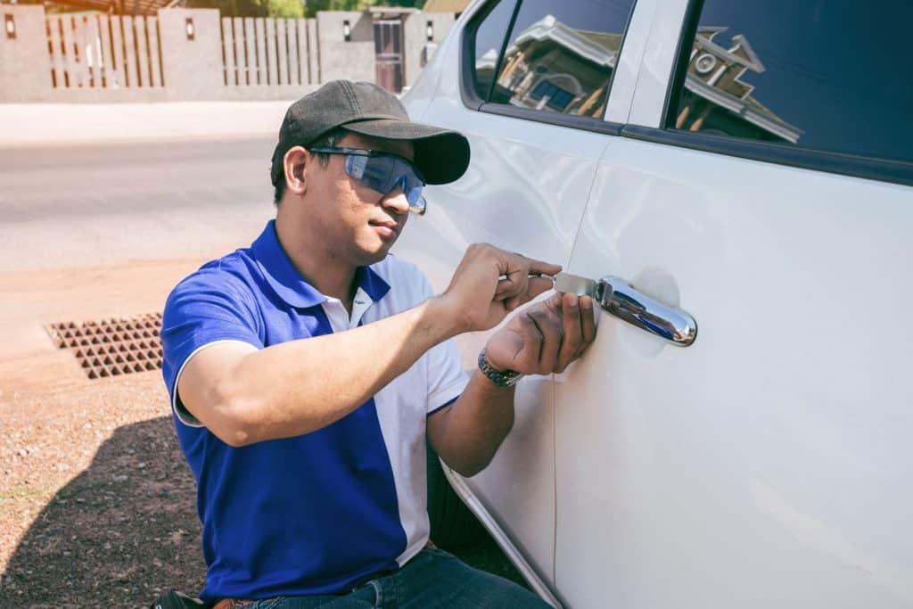 A man opening a car door using a lockpicker