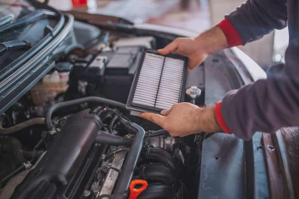 Mechanic holding and removing a car air filter, How Much Does It Cost To Replace Engine Air Filter?