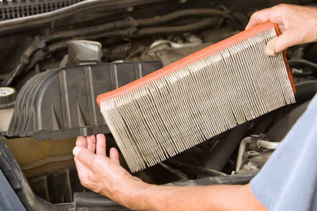 A mechanic removing an old dirty air filter