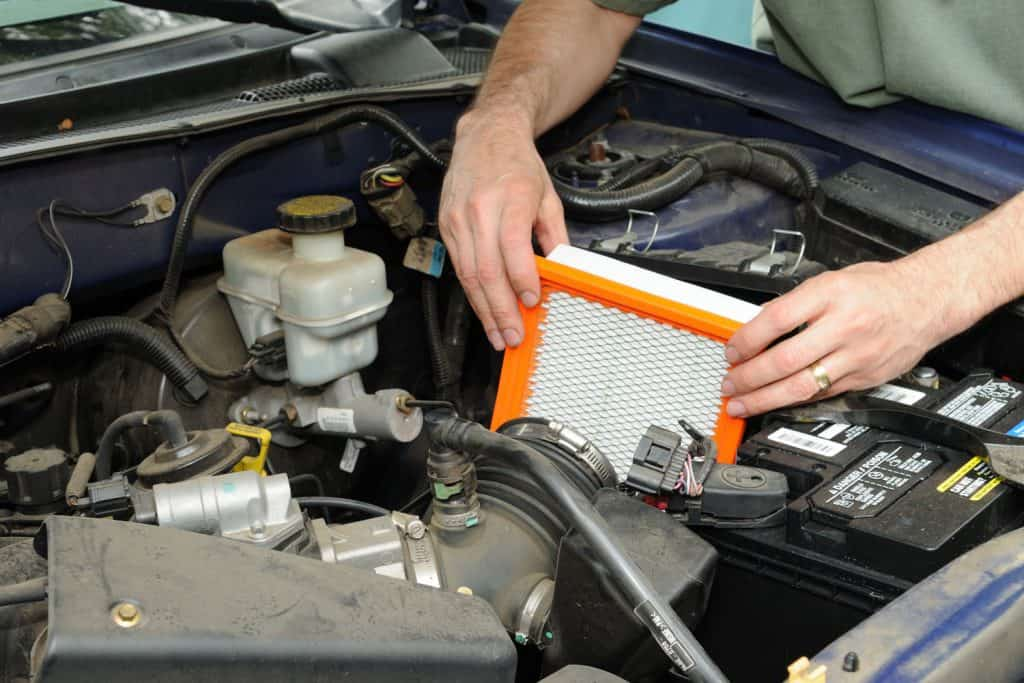 A mechanic replacing an old car air filter with a new one