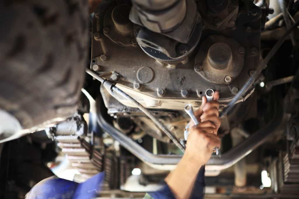 A motor mechanic is working on a gearbox under a Heavy goods truck in a pit of a workshop with a socket wrench